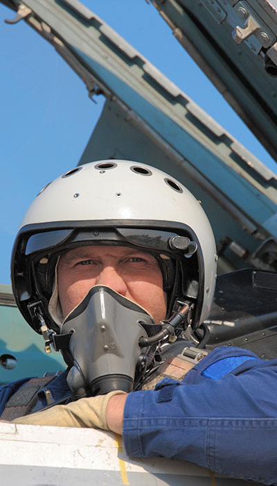 pilot guy wearing a mask squinting his eyes looking out from plane jet with arm over edge lone star industry